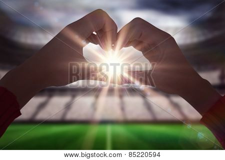 Woman making heart shape with hands against football stadium with fans in white