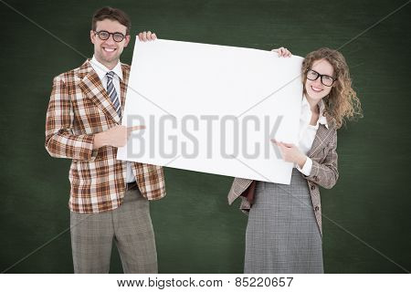 Geeky hipster couple holding poster against green chalkboard