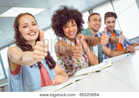 Fashion student smiling at camera with thumbs up at the college