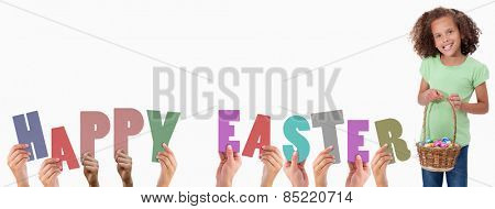 Hands holding up happy easter against portrait of a young girl holding a basket full of easter eggs