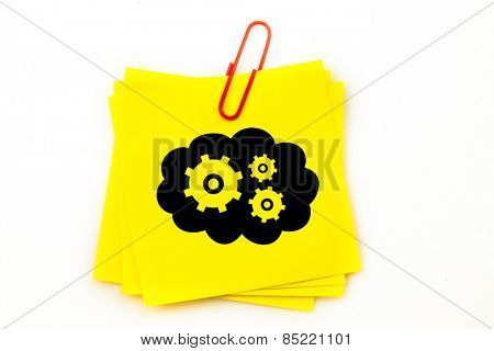 Cogs and wheels in cloud against sticky note with red paperclip