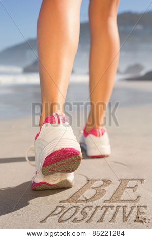 Fit woman walking on the beach against be postive