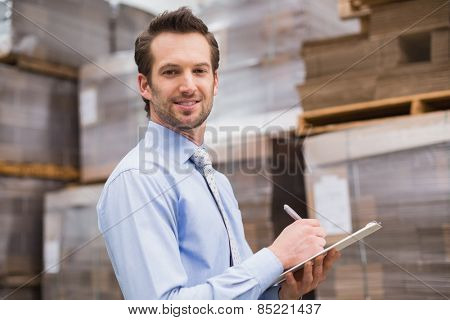 Handsome warehouse manager smiling at camera in warehouse