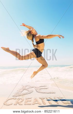 Fit blonde jumping gracefully on the beach against be creative