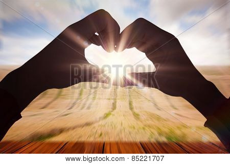 Woman making heart shape with hands against wooden planks overlooking corn field
