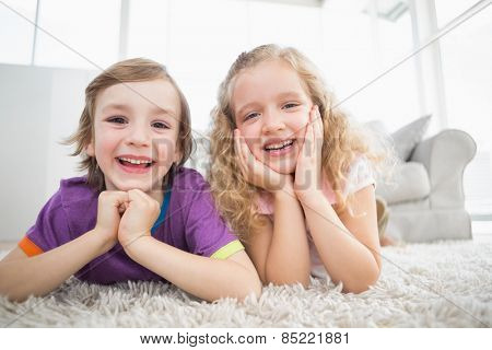 Portrait of happy siblings lying on rug at home