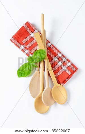 wooden spoons and fresh basil on checkered dishtowel