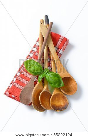 old wooden spoons and fresh basil on checkered dishtowel