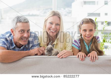Portrait of happy family with rabbit on sofa at home