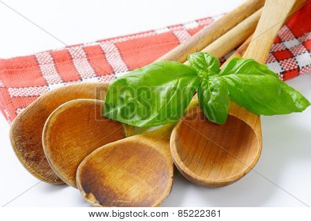 close up of old wooden spoons and fresh basil on checkered dishtowel