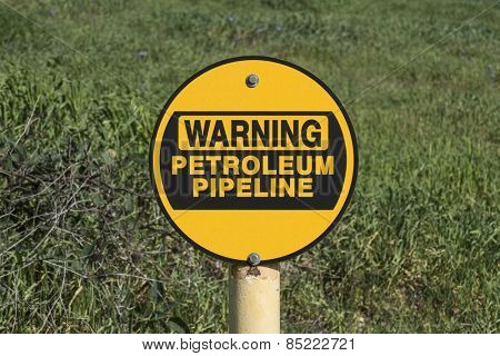 Petroleum pipeline warning sign in green grassy meadow.