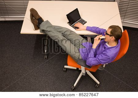 Healthy snack in workplace. Man sitting at with legs on the desk with tablet, eating corn waffle  in office