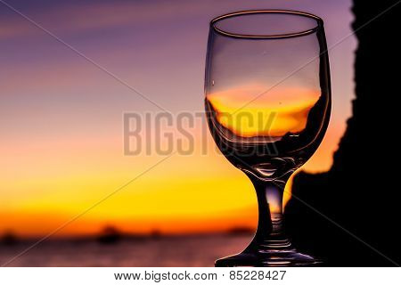 tropical sunset on beach reflected in a wine glass, summertime vacation concept
