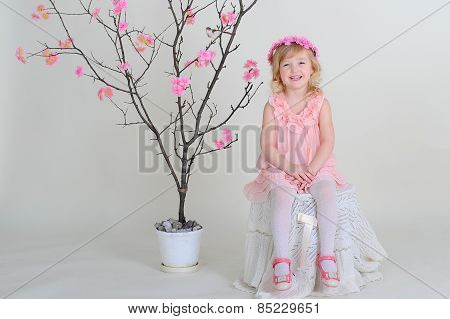 Girl In A Pink Wreath And A Pink Dress With A Bird On A Flowering Tree. Laughs
