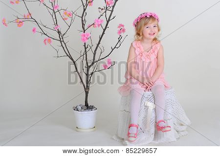 Girl In A Pink Wreath And A Pink Dress With A Bird On A Flowering Tree. Smiling