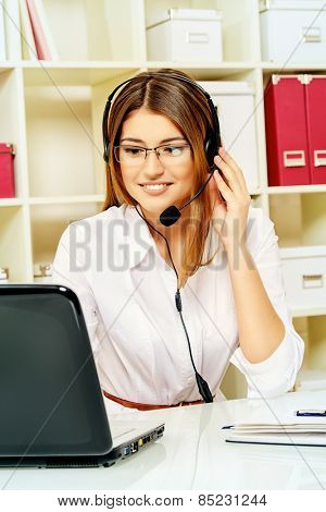 Happy smiling young woman surrort phone operator at her workplace in the office. Headset. Customer service.