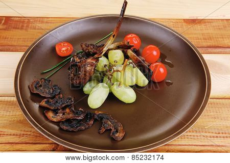 meat ribs on dish with tomatoes on table