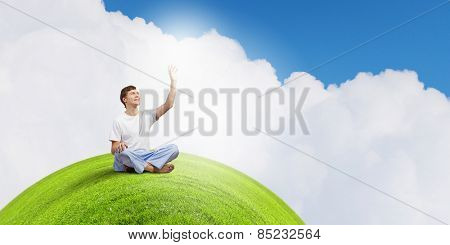 Young smiling guy sitting in lotus pose and meditating