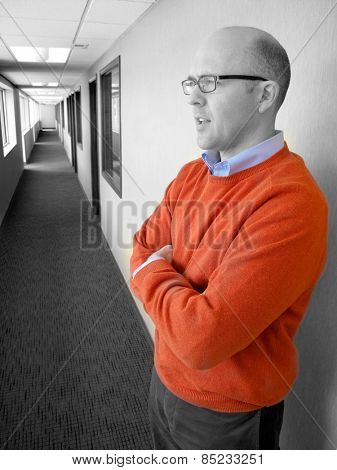 Man Standing in Hallway Wearing Orange Sweater
