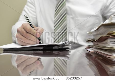 Businessman sitting at desk with pad of paper and piles fileswriting