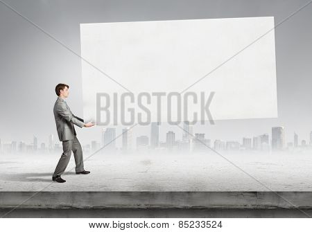 Tired businessman carrying big blank banner. Place for your text