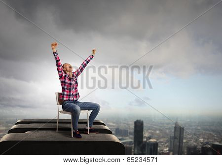 Young woman in casual with arms up celebrating success