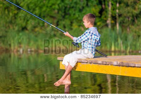 Boy in blue shirt sit on a pier with a fishing rod by the sea