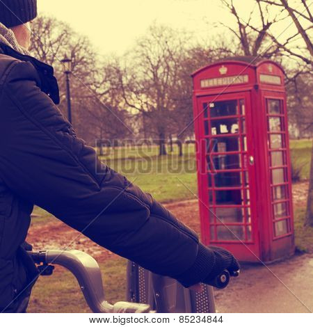 a young man riding a bicycle in Hyde Park in winter in London, United Kingdom, with a typical red telephone booth in the background