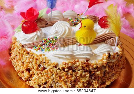 closeup of a mona de pascua, a cake eaten in Spain on Easter Monday, ornamented with feathers and a teddy chick