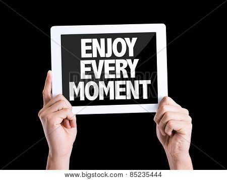 Tablet pc with text Enjoy Every Moment isolated on black background