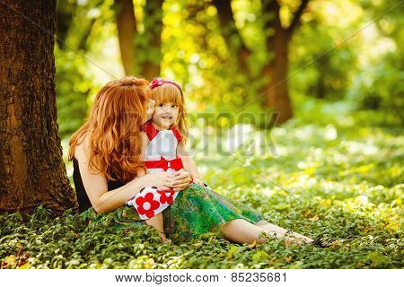 Mother and her little daughter on a walk in the park in the summer.