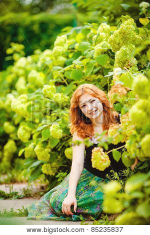 Beautiful red-haired woman on a background of green flowering shrubs.