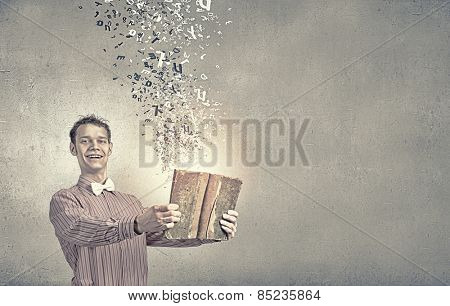 Young funny science man with book in hands