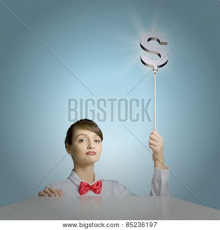 Young woman holding balloon shaped like dollar sign