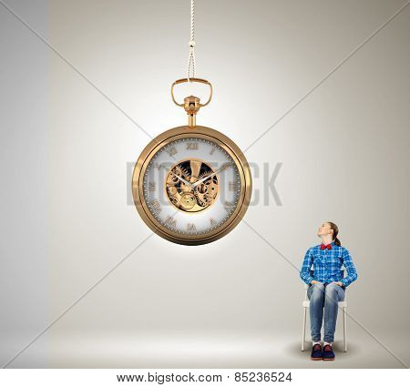 Young woman in casual looking at pocket clock