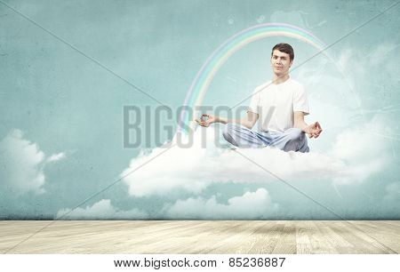 Young smiling guy sitting on cloud and meditating