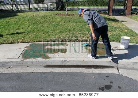 Lake Forest California - March 010,.2015 : Workers use hot water steam pressure washers and paint remover to eliminate graffiti spray painted on to a city sidewalk.