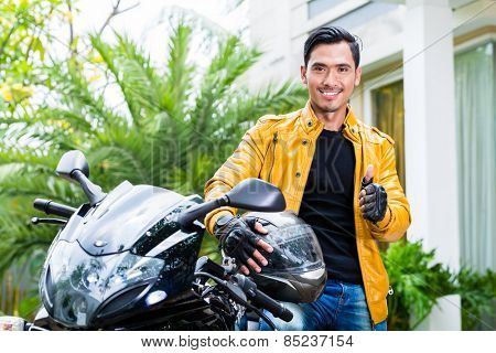 Asian young man and his motorcycle or scooter
