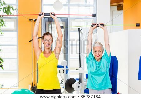 Senior and young woman on fitness ball training arm muscles with rod in gym or health club