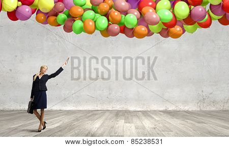 Young businesswoman with suitcase and bunch of colorful balloons