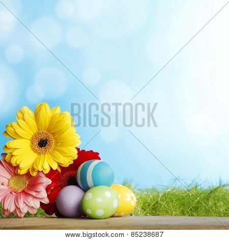 Beautiful painted easter eggs and flowers over geen meadow background