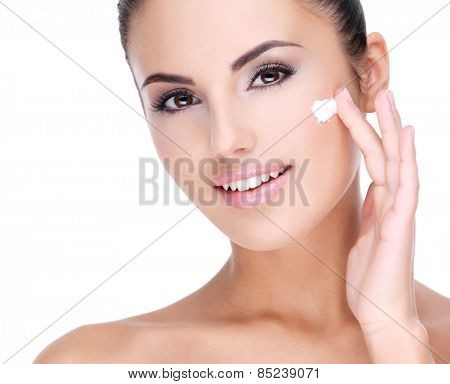 Young smiling  woman with cosmetic  cream on a pretty fresh face - isolated on white