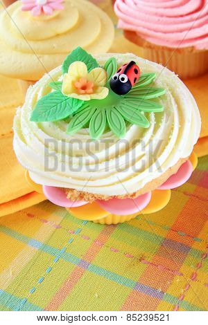 Spring cupcake with a flower and ladybug made of fondant.