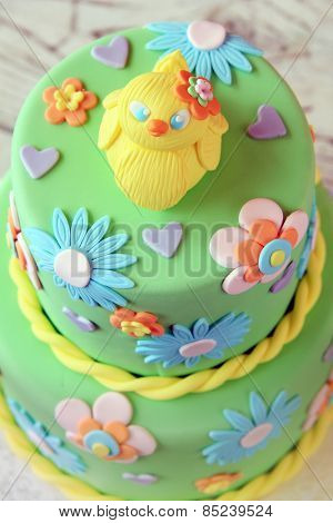 Easter fondant cake with an Easter chick on top.