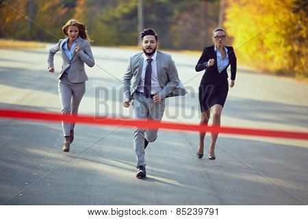 Businessman competing with two businesswomen