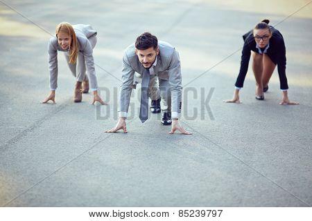 Three businesspeople ready to run