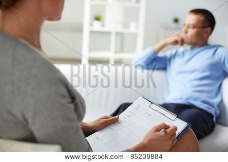 Woman psychologist filling in card of her patient