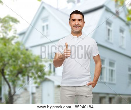happiness, gesture and people concept - smiling man showing thumbs up over house background