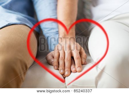 people, homosexuality, same-sex marriage, valentines day and love concept - close up of happy male gay couple holding hands with red heart shape