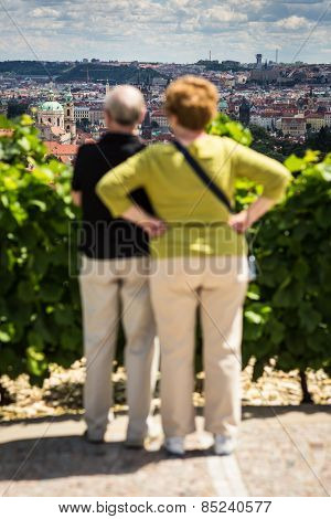 Couple of elderly tourists admiring the view of Prague (Prague, Czech republic)